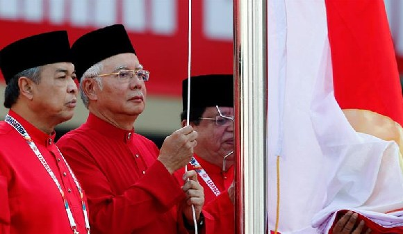 Ahmad Zahid Hamidi, left, raising the UMNO flag with former PM Najib