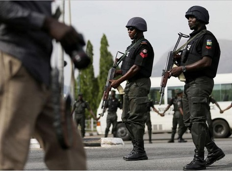 Police officers patrol near a journalist during a protest by the Abuja