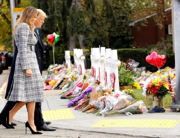 U.S. President Donald Trump and Melania Trump pay their respects at a makeshift memorial