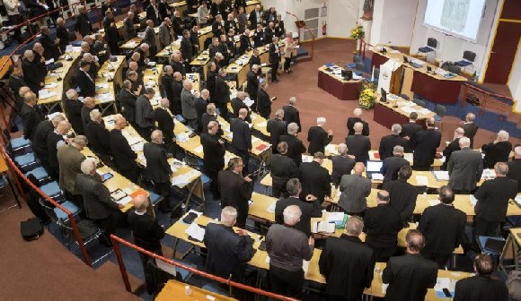 French bishops stand in prayer at the opening of the French Bishops Conference