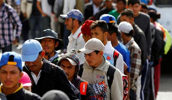 Migrants and refugees stand in line for a meal after arriving in Tijuana, Mexico