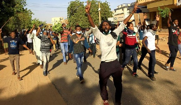 Demonstrators chant slogans as they march along the street during anti-government protests