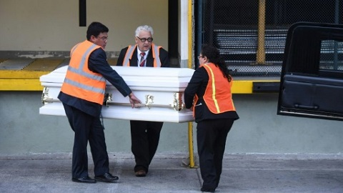 Employees of a funeral home carry a coffin with the repatriated remains of 7-year-old Jakelin Caal