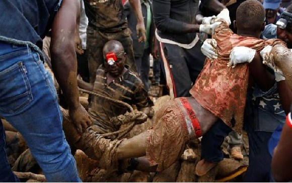 A rescued miner being carried from a pit at the mining site on Saturday