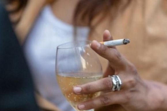 A lady holding a cigarette and a glass of wine