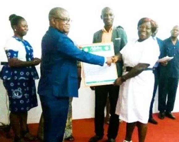 Timothy Letsa (left) presenting a citation to Ms Catherine Abena Adobea, best worker for 2018