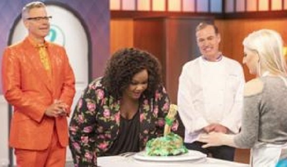 Nicole Byer inspecting a creation on the baking contest
