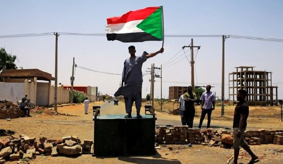 A Sudanese protester stands on a barricade in Khartoum on Wednesday