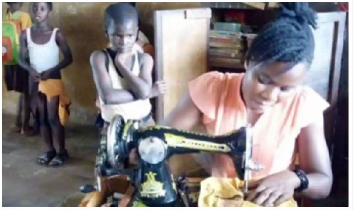 Miss Naomi Awomeh busy sewing the uniforms during her break time