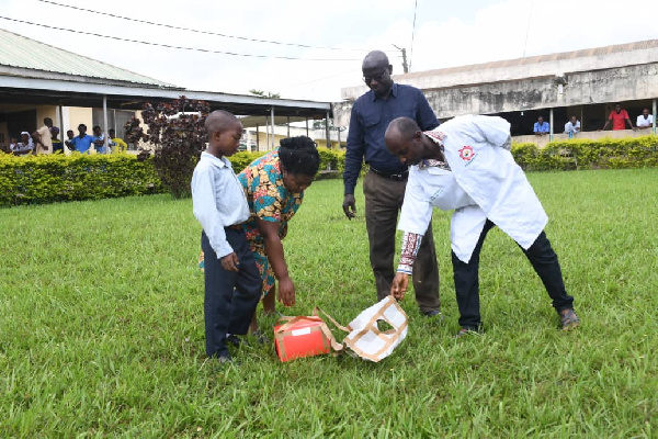 The boy's mother taking the medicine after the drone landed at the hospital
