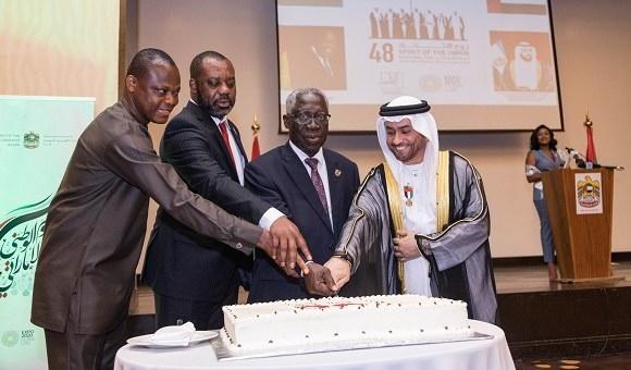 The Ambassador assisted by other dignitaries cutting cake at the event