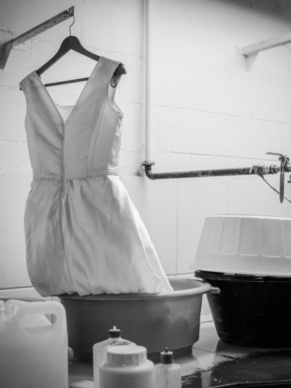 Fotografía en branco e negro dun traxe de noiva colgado en proceso de limpieza. Tintorería Moderna