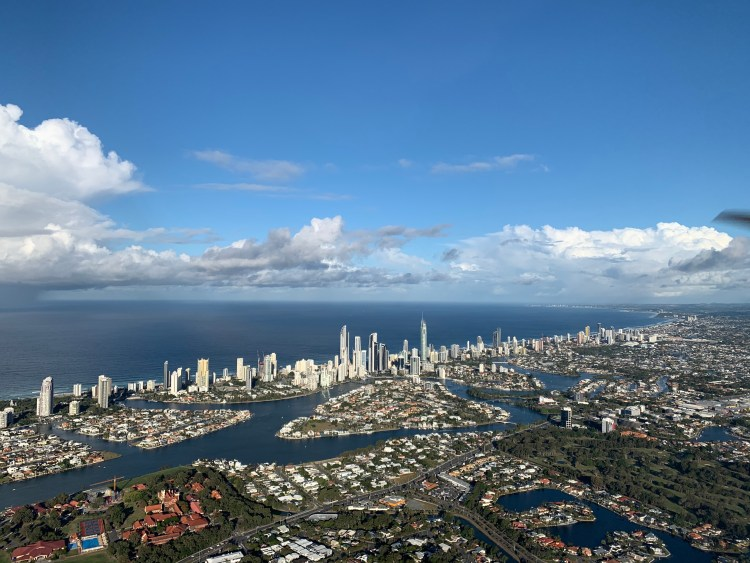 Scenic view of a coastal city with blue skies and white clouds, a view you can see with our A.S. Flying School Discovery Flight