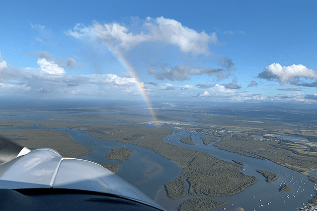 Scenic shot from a plane looking down at marshes and rivers with a rainbow in a cloudy blue sky