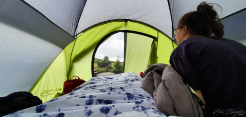 woman looking at the view from inside a tent