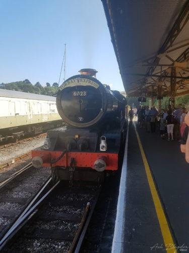 Steam train on platform blue sky