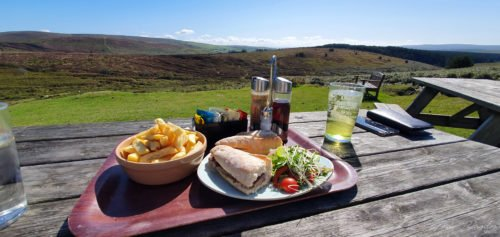 a table with a plate of food and a drink with a view at Warren House Inn