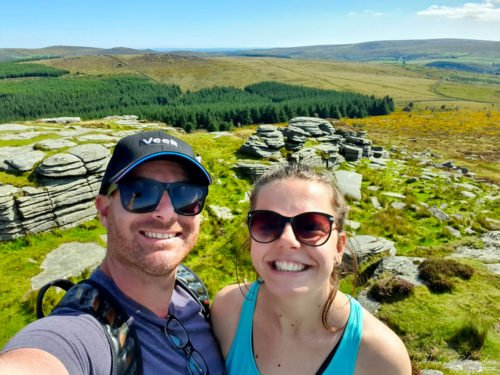 Couple people on top of rocks tor with forest