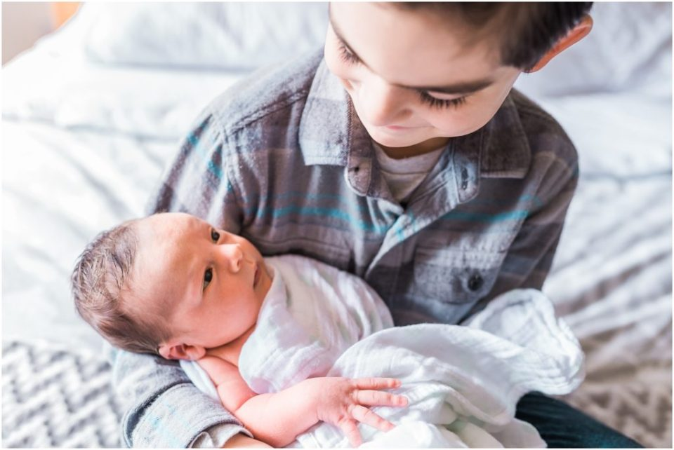 older brother holding newborn brother