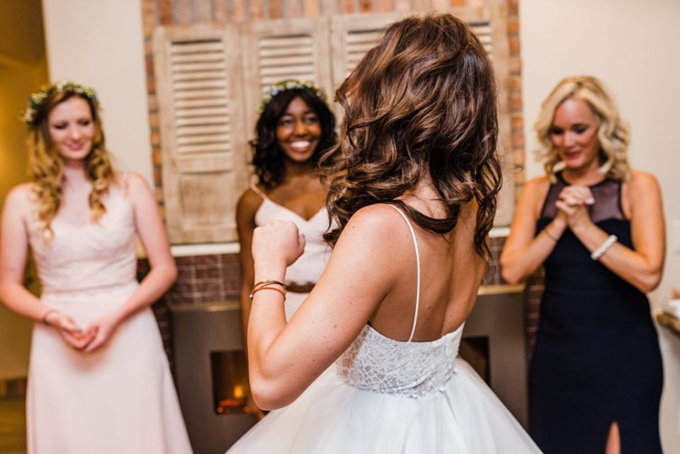 bridesmaids watching bride get dressed