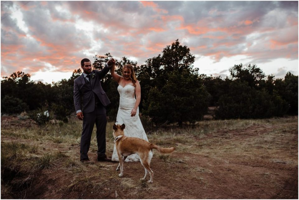 bride and groom dancing at sunset with their dog
