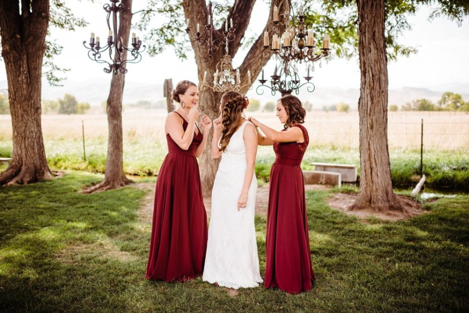 bridesmaids helping bride get dressed outside
