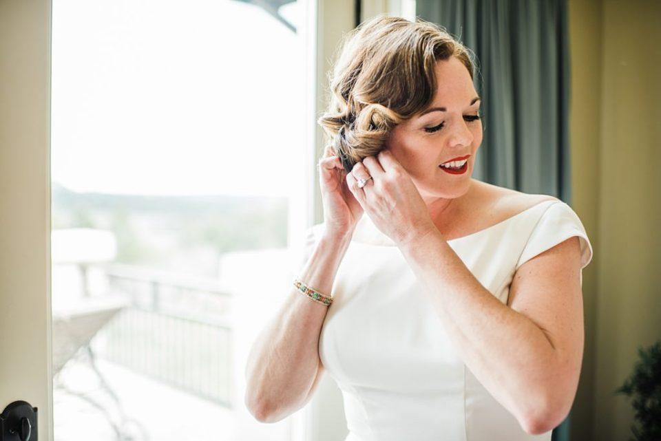 bride putting earrings on