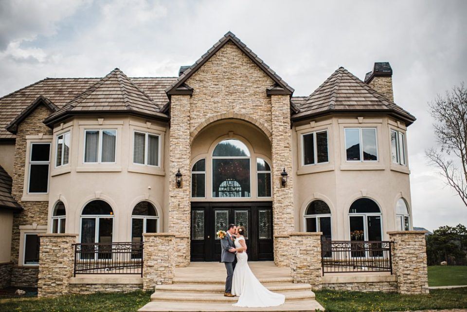 bride and groom in front of colorado estate