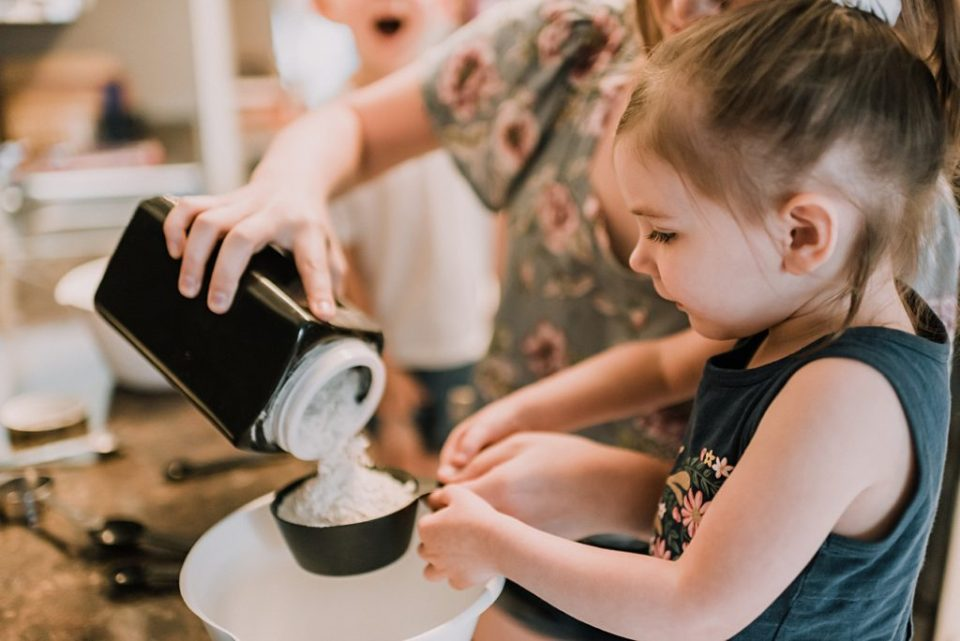 little girl holding measuring cup while making waffles with mom