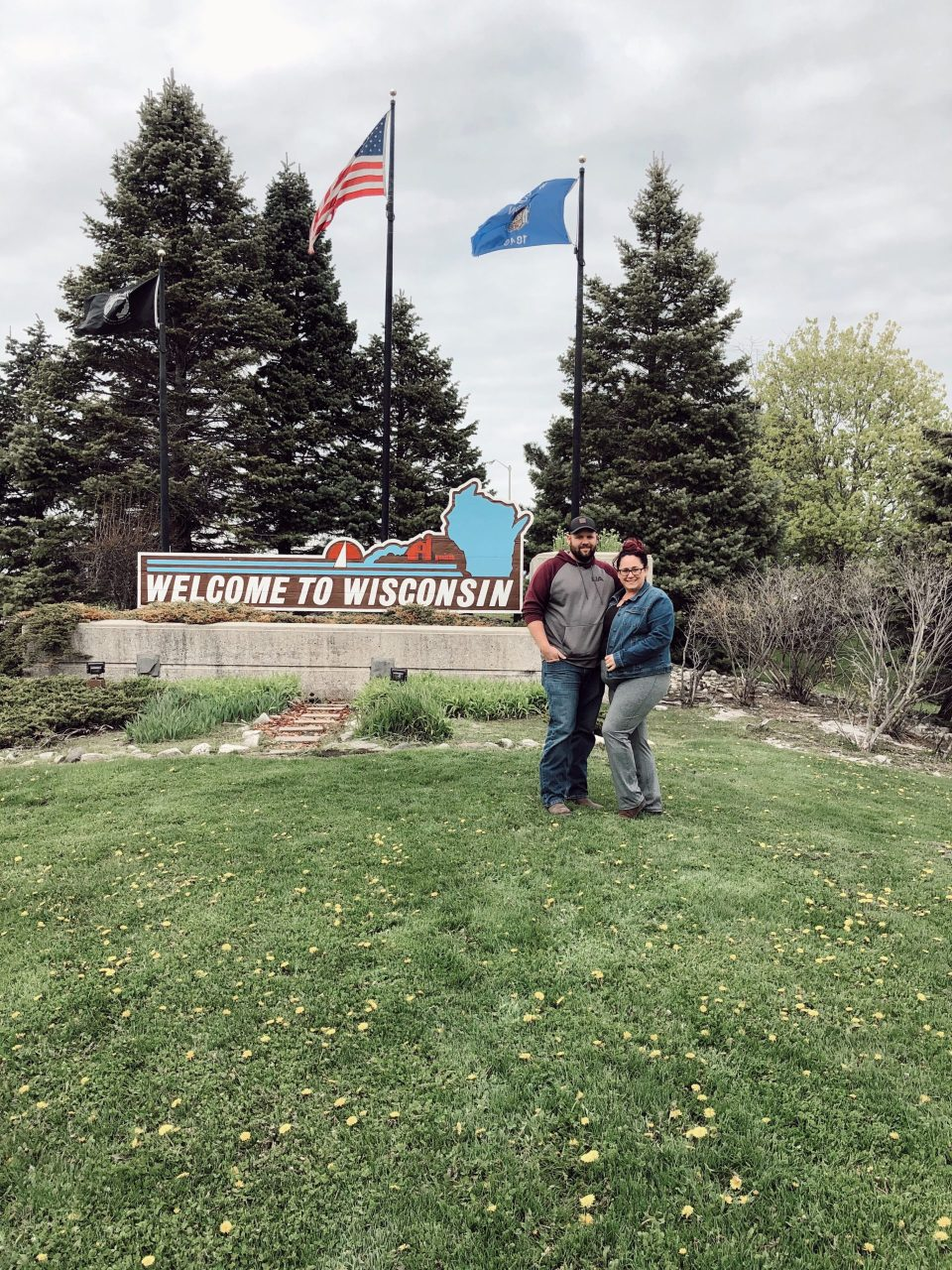 family in front of wisconsin sign