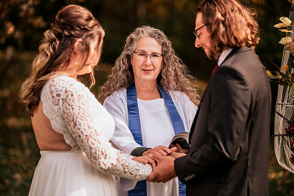 officiant praying over bride and groom
