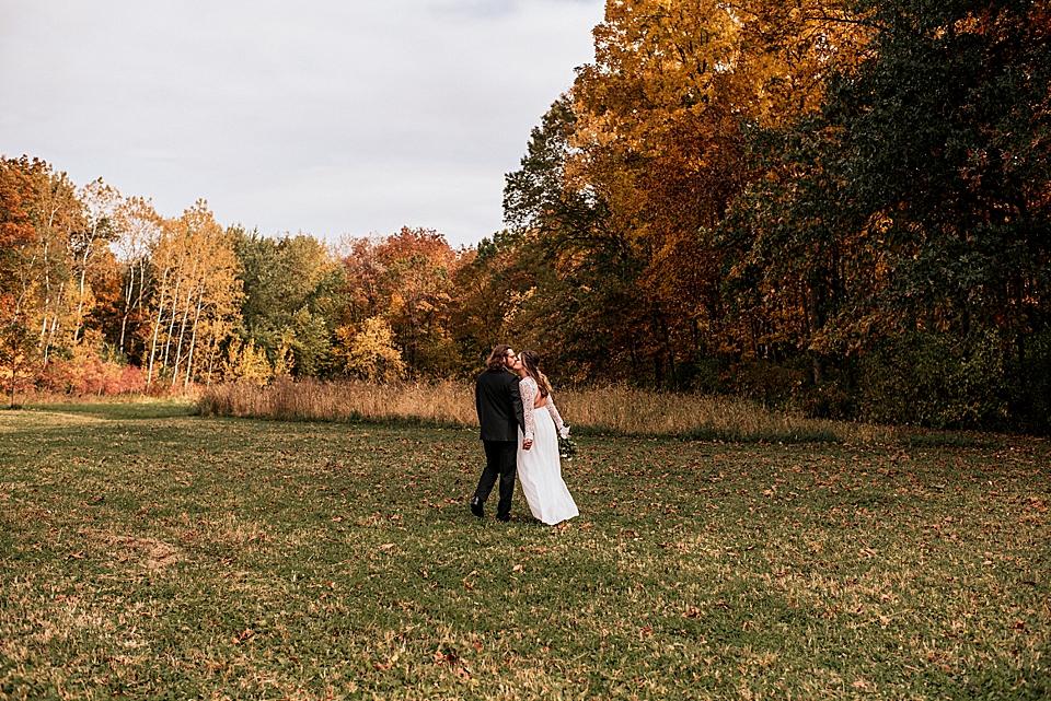 kissing couple walking toward autumn forest