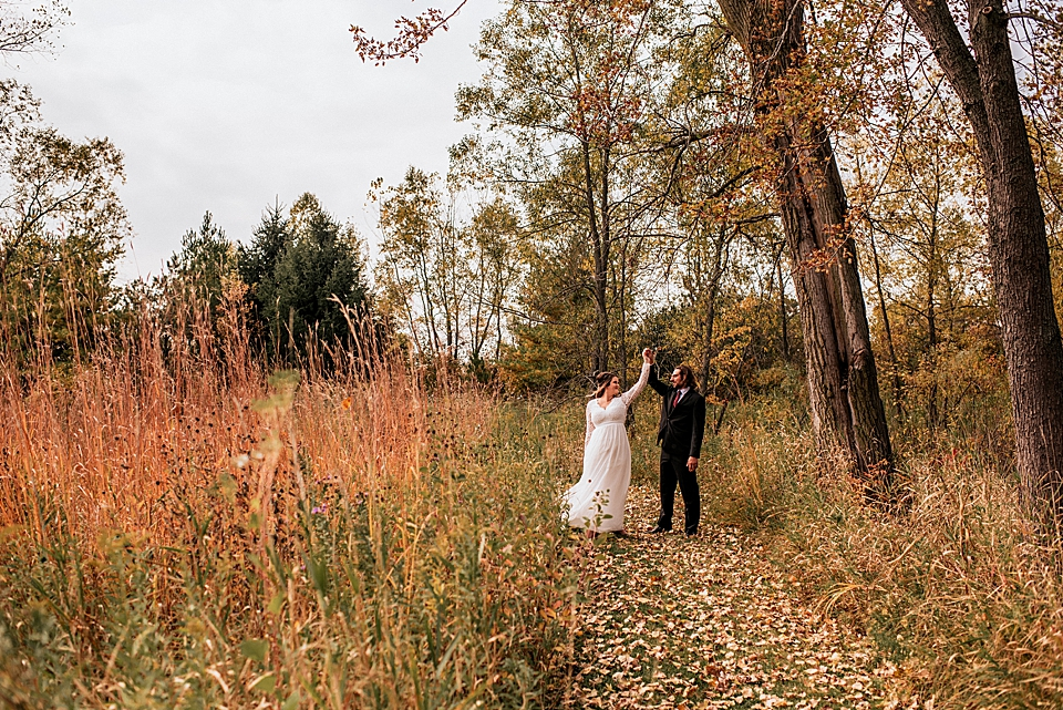 bride and groom dancing in the fall foliage