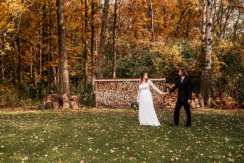 bride and groom walking in front of wood pile