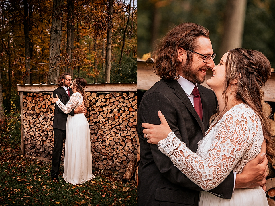 newlyweds kissing in front of the wood pile
