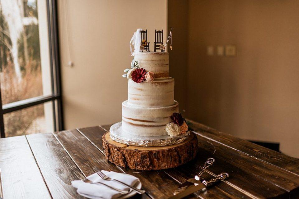 naked wedding cake with fishing rod cake topper