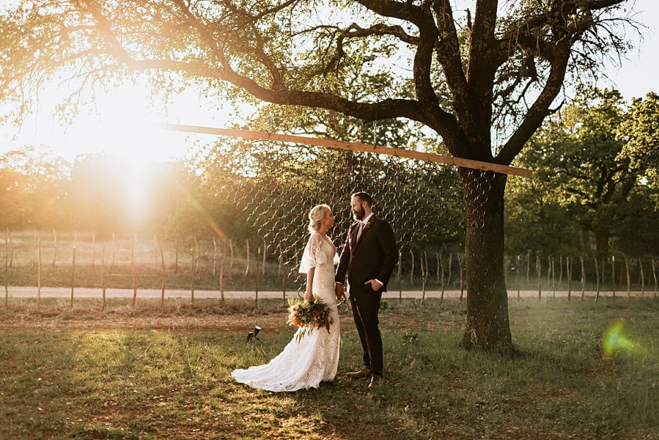 bride and groom in front of a ring backdrop