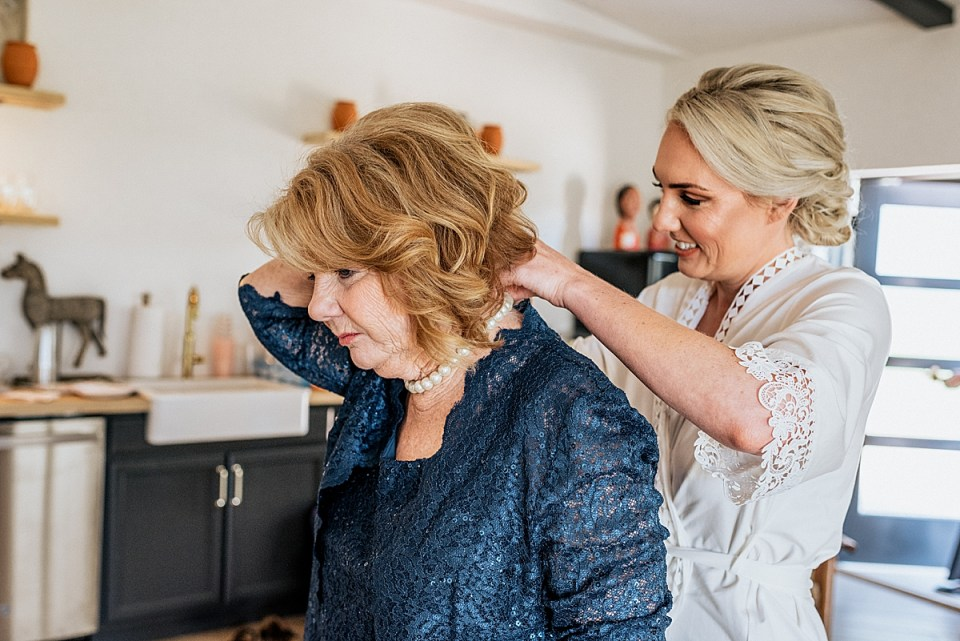 bride putting makeup on her mom