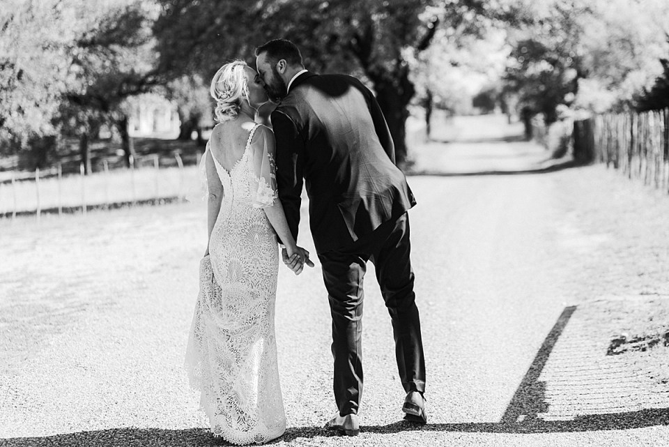 black and white image of bride and groom walking and kissing from behind