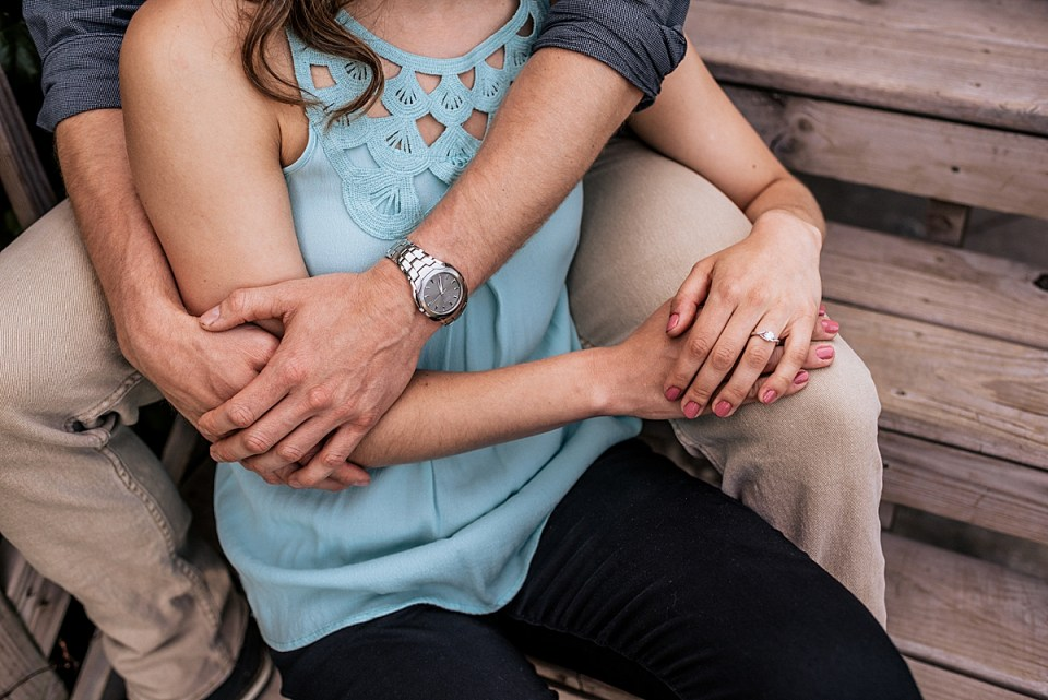 couple snuggling showing off engagement ring and watch