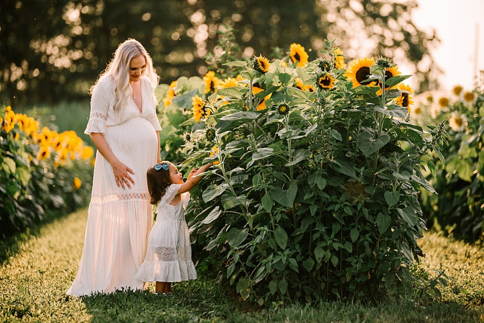 mother and toddler in sunflower field
