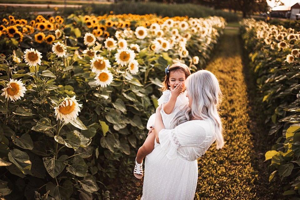mom and baby girl snuggling in a field of sunflowers