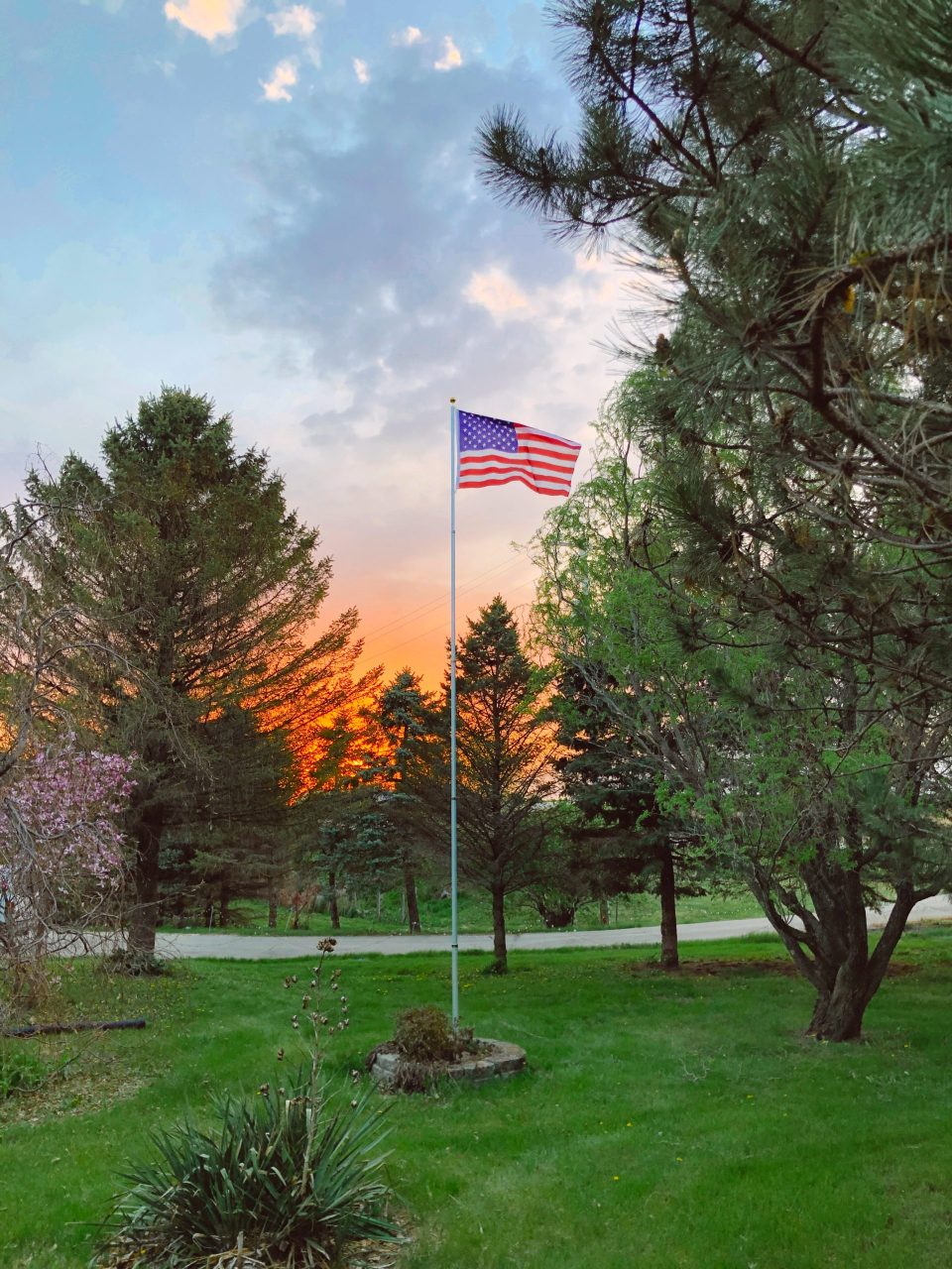 american flag waving in the sunset