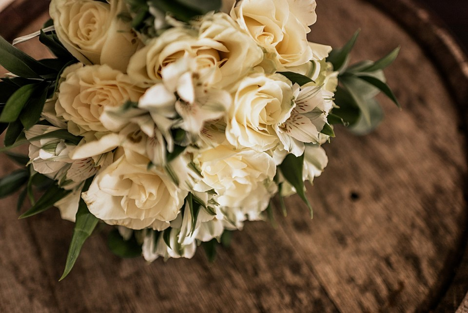 white bridal bouquet on a whiskey barrel