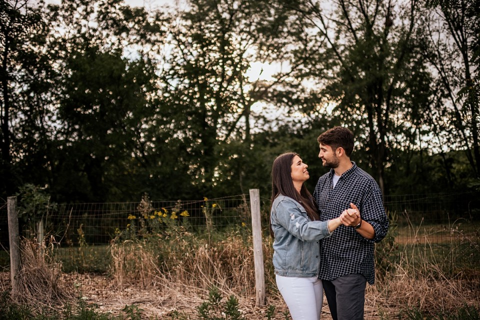 couple kissing and walking through a field