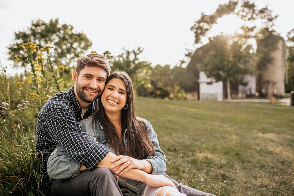 couple snuggling together with a barn in the background