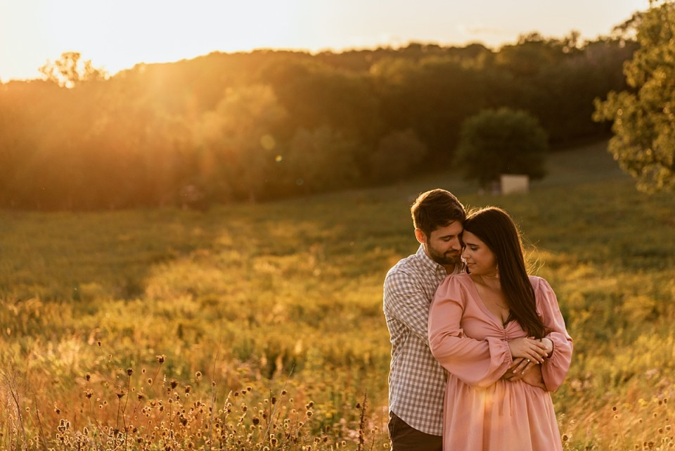 couple wrapped into each other for sunset engagement photos