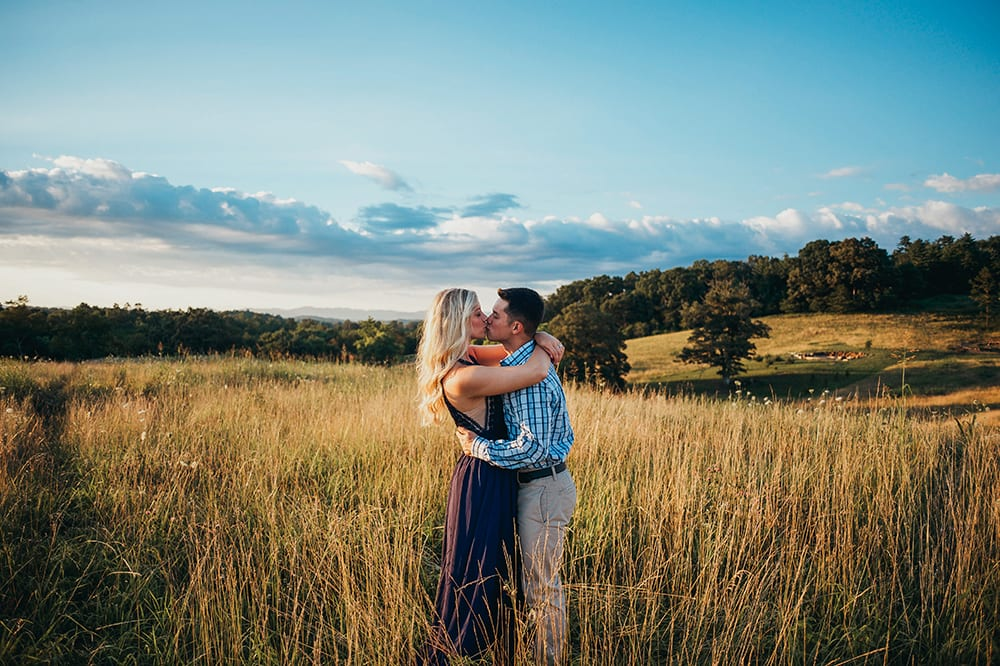 Engaged couple shares an embrace in a mountain field outside of Asheville, NC.