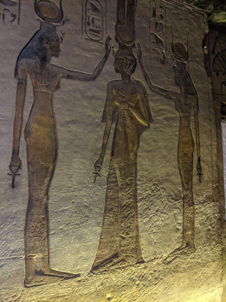 Hathor (goddess with cow horns and sun plate), Nefertari, and goddess Isis