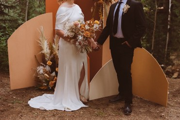 Bride and groom standing in front of a floral and wood arch in the forest | Floral arch detail | Elopement decor | Wedding decor | Wedding portraits | Elopement portraits | Bride and groom elopement photos | Elopement wedding photos in Colorado | Colorado wedding photos | Colorado elopement photos | Elopement at Treehaus, Colorado | Treehaus Colorado | Colorado elopement | Treehaus elopement | Colorado elopement venue | Colorado mountain elopement venue | Unique elopement venue | Elopement venue in Colorado | Ashley Joyce Photography 2020